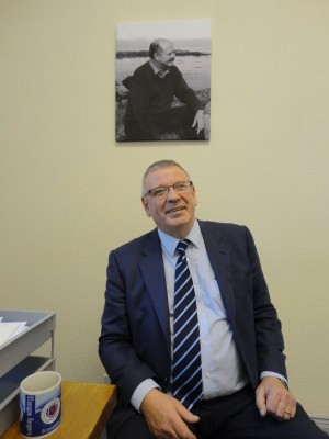 Brian Ervine sitting below portrait of his brother David Ervine