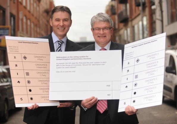 Chief electoral officer Graham Shields and head of the Electoral Commission in NI Séamus Magee posing with enormous ballot papers