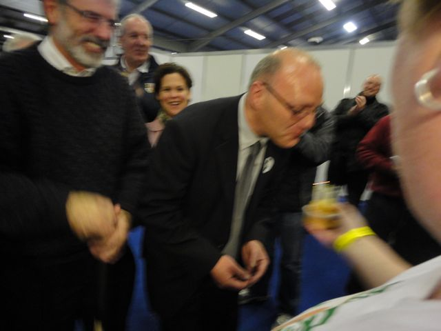 Paul Maskey blowing out candles on a muffin - it's his birthday