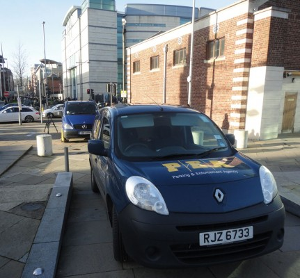 media vehicle being unclamped across the road from Belfast courts