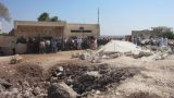 Residents queueing for bread in Ma'arat Misrin, next to a large crater from a recent air strike, Syria, Sep 2012 © Amnesty International