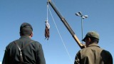 Iranian soldiers watch a man being hanged in Shiraz, south of Tehran © AFP/Getty Images