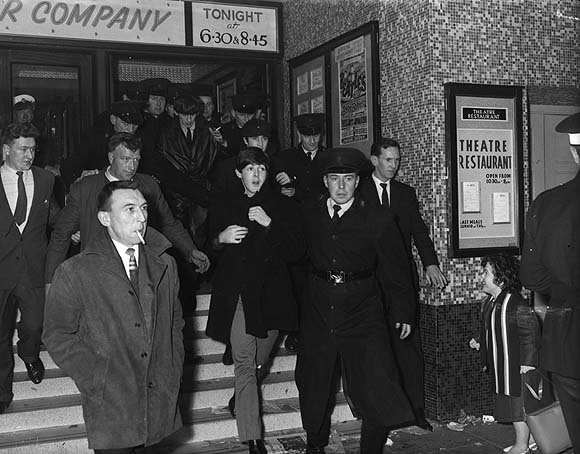 The Beatles, flanked by RUC officers, on their way to their second and final Belfast concert, at the Ritz cinema, 8 November 1964