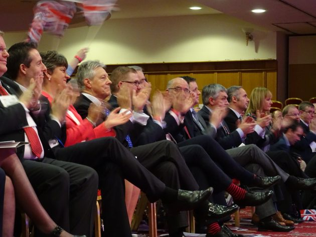 Peter Robinson being applauded after a mention on stage dup15