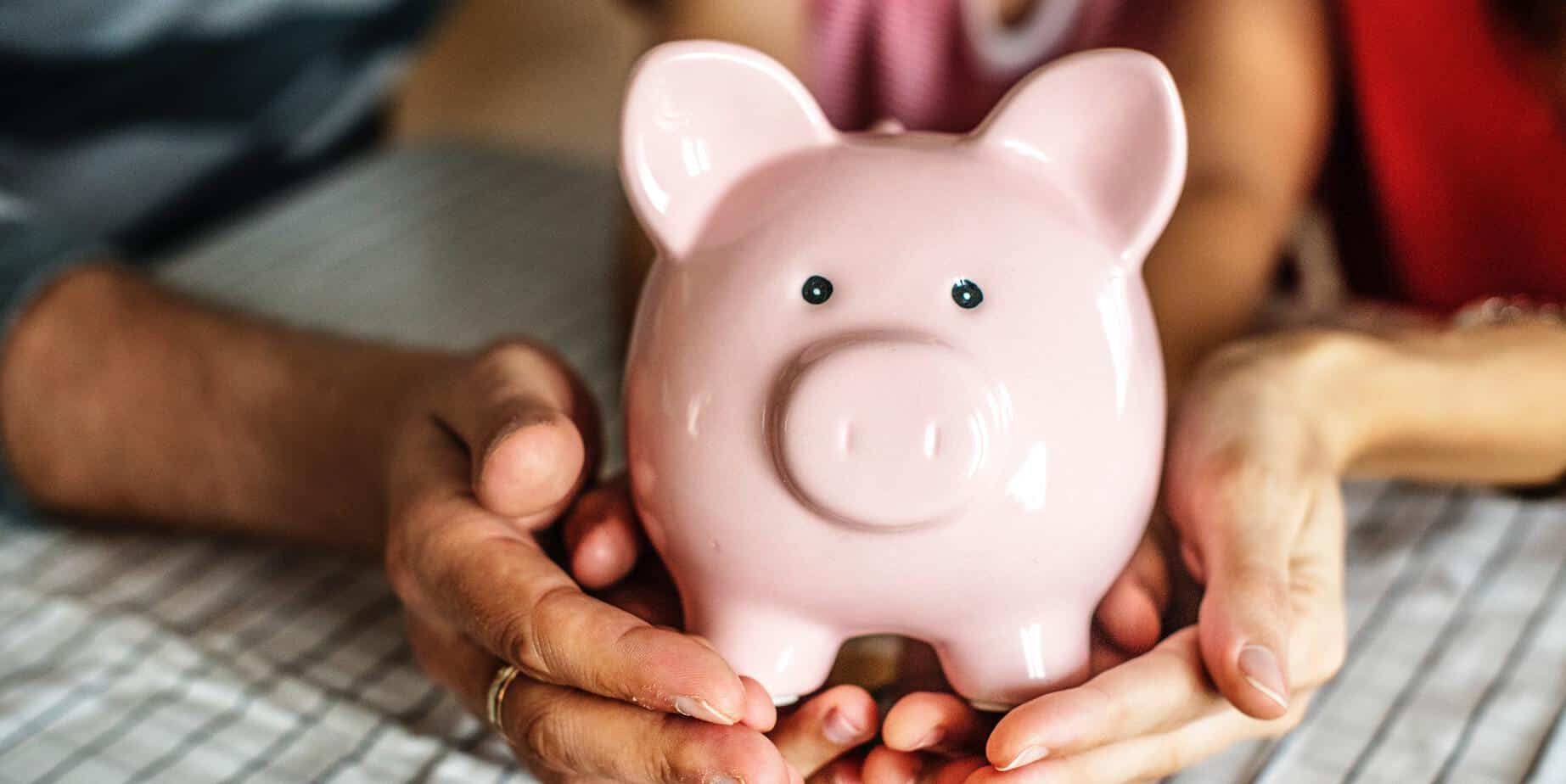 Picture of piggy bank being held by different ages of hands - Photo by rawpixel.com from Pexels