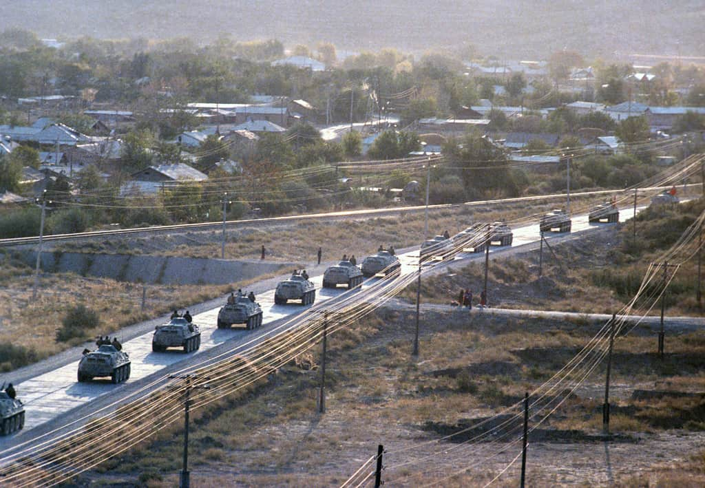 Soviet APCs depart Afghanistan as part of the first phase of troop withdrawal in 1986.