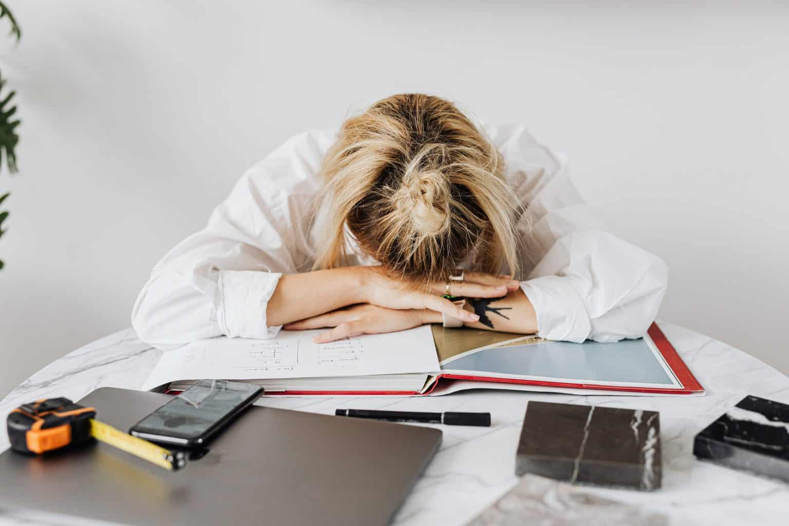 Woman in white robe writing on white paper